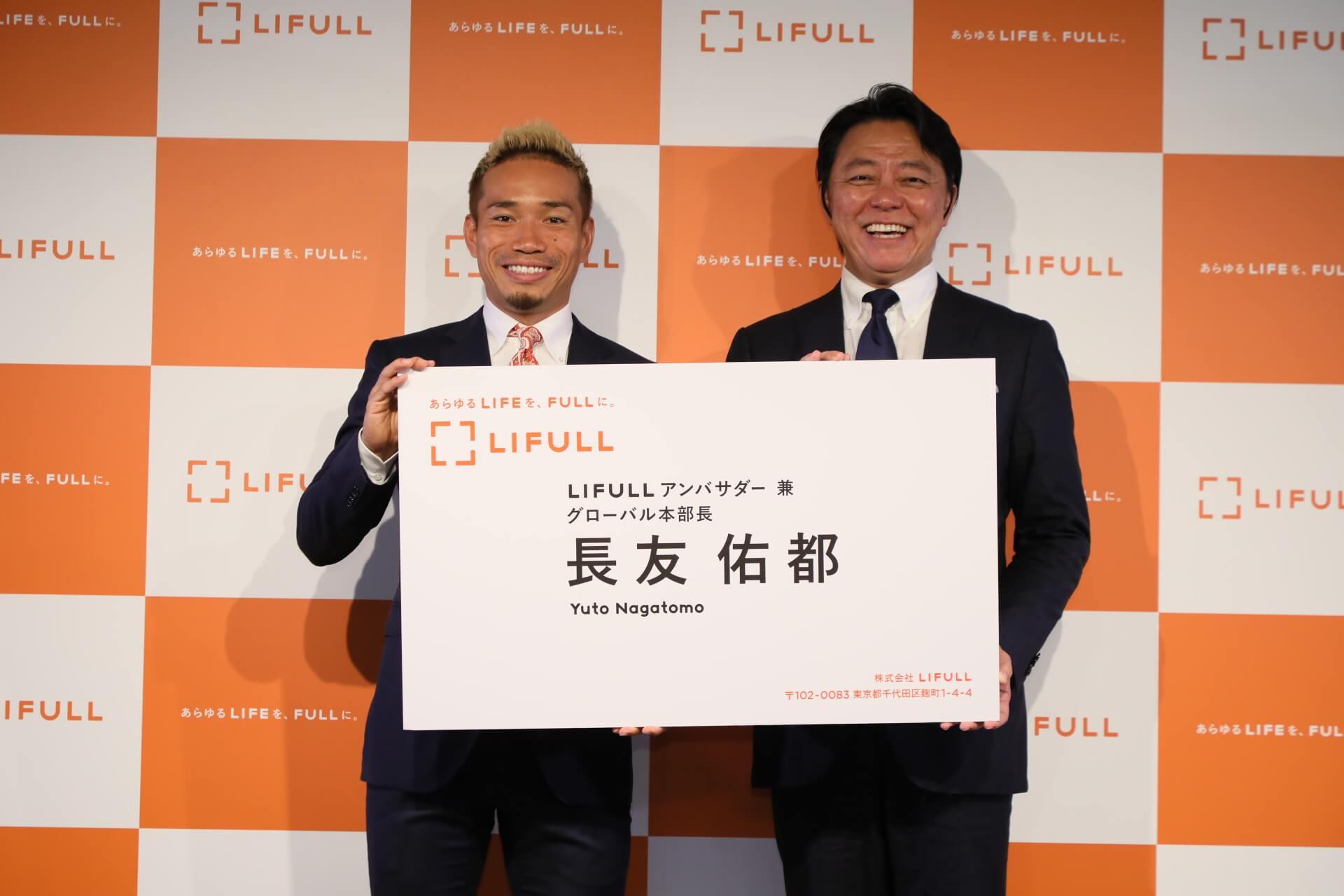 Yuuko Nagatomo (left) receives a commemorative card from Lifull CEO Takashi Inoue